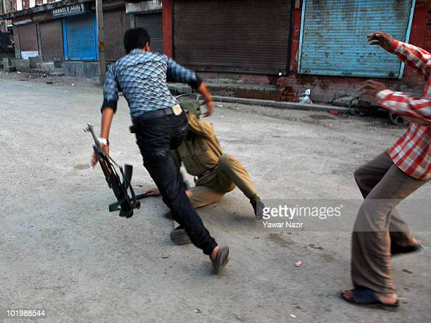 Kashmiri Muslims chase and beat an Indian policeman after a 17 year old teenager Tufail Ahmad was killed during a clash with police after prayers on...