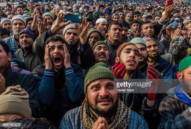 Kashmiri Muslims devotees pray while looking towards a cleric displaying the holy relic believed to be of Sufi Saint outside the Dastgeer Sahib...
