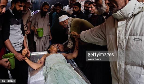Kashmiri Muslims give customary bath to Qaisar Sofi a 16 year old boy during his funeral on November 05 2016 in Srinagar the summer capital of Indian...