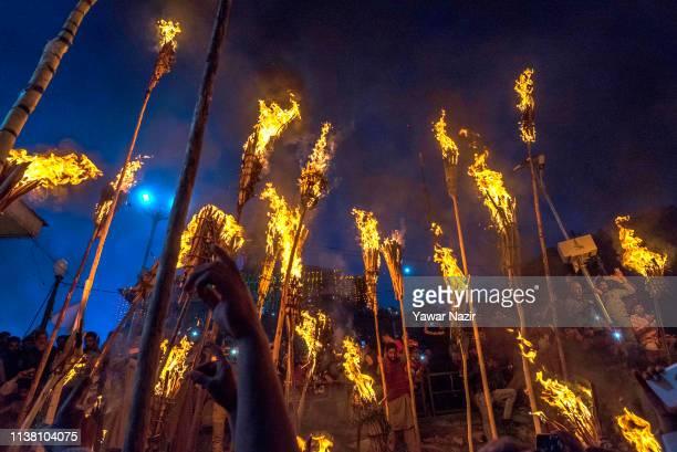 Kashmiri Muslims hold burning torches outside the cave shrine of Sakhi Zainuddin Wali a Sufi saint during an annual torch festival in Aishmuqam 75 km...