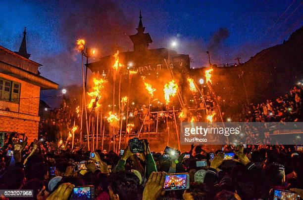 Kashmiri Muslims hold the burning torches outside the cave shrine of Sakhi Zainuddin Wali a Sufi saint during an annual torch festival in Aishmuqam...