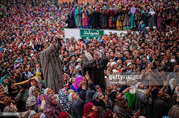 Kashmiri Muslims look towards a cleric displaying the holy relic believed to be the hair from the beard of the Prophet Mohammed at Hazratbal shrine...