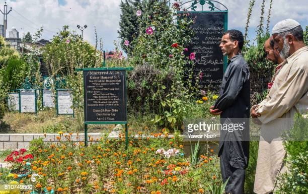 Kashmiri Muslims offer prayers at the martyrs graveyard during a curfew on the the first death anniversary of Burhan Wani a young rebel commander on...