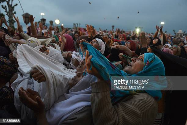 TOPSHOT Kashmiri Muslims pray as an unseen custodian displays a holy relic believed to be a hair from the Prophet Muhammad's beard during...