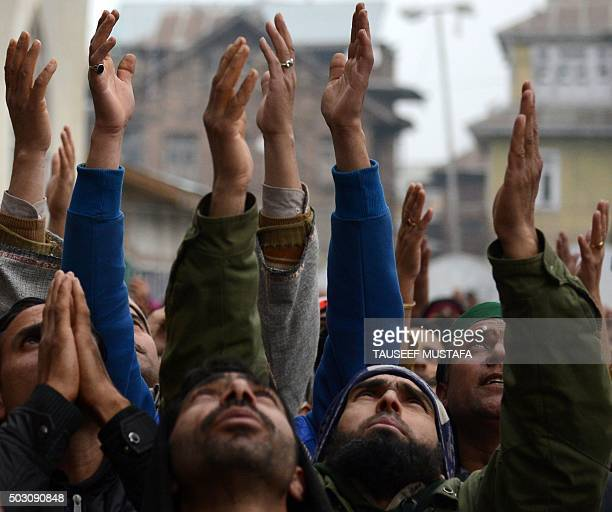 Kashmiri Muslims pray as unseen priest shows a relic believed to be a hair from the beard of the Prophet Muhammad at the Hazratbal Shrine in Srinagar...