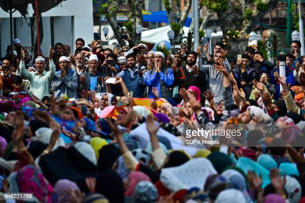 Kashmiri Muslims raise their hands in prayer on seeing a relic beleived to be hair from the beard of Prophet Muhammad on the occasion of the Islamic...