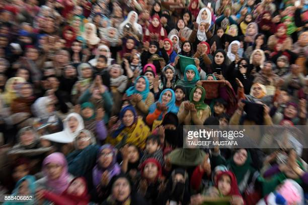 Kashmiri muslims react as a priest displays a relic believed to be a hair from the beard of Prophet Muhammed during the last friday of...