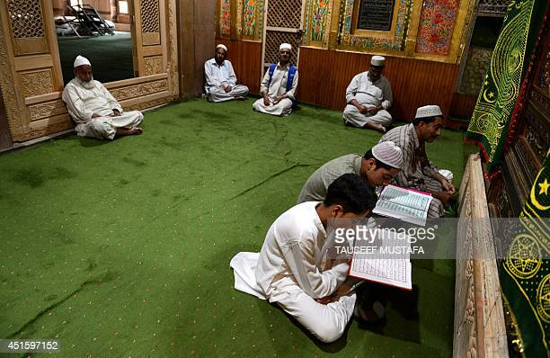 Kashmiri Muslims read the Koran Islam's holy book during the holy month of Ramadan at the Naqashband Sahib Shrine in Srinagar on July 2 2014 Across...