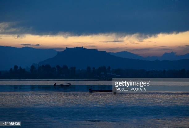 Kashmiri Muslims row a boat on Dal Lake in Srinagar on September 1 2014 Kashmir is divided between nucleararmed rivals India and Pakistan with both...
