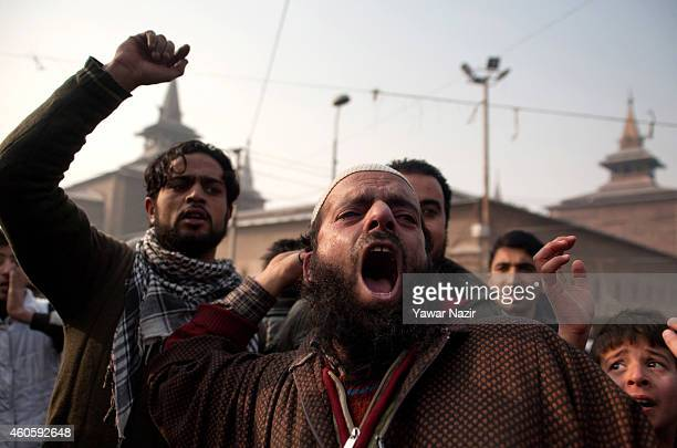 Kashmiri Muslims shout anti terrorism slogans during the funeral prayers in absentia for the victims killed in a militant attack in Peshawar at Grand...