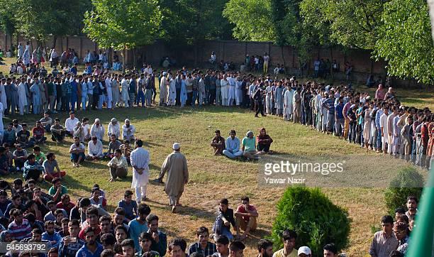 Kashmiri Muslims wait in queue to get a glimpse of Burhan Muzaffar Wani a top Hizbul Mujahideen commander as they attend the funeral of Wani al on...