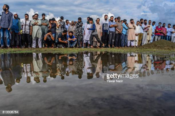 Kashmiri Muslims wait to offer the funeral prayers of slain rebel Sajjad Ahamd killed in a gun battle with Indian government forces during his...