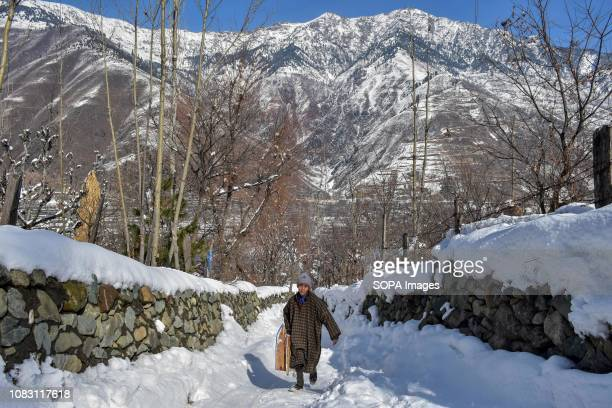Kashmiri nomad seen holding his sledge as he walks through snow during a sunny winter day in Ganderbal about 50kms from Srinagar Indian administered...