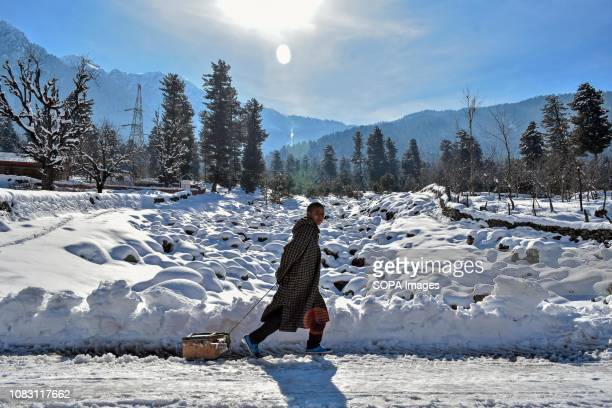 Kashmiri nomad seen pulling his toboggan through snow during a sunny winter day in Ganderbal about 50kms from Srinagar Indian administered Kashmir...