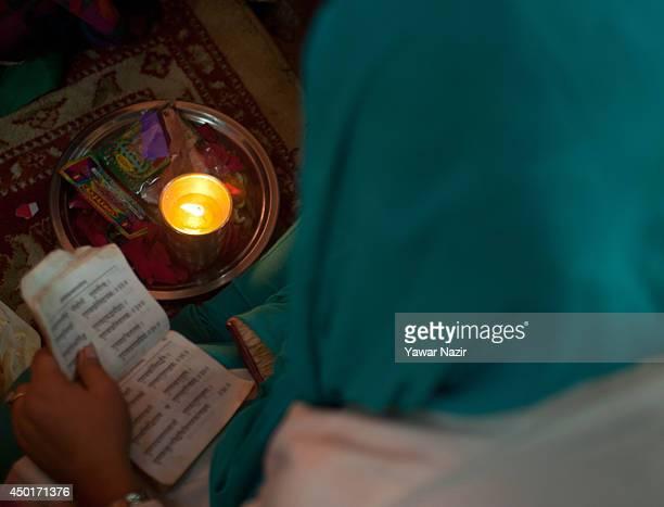 Kashmiri Pandit woman devotee reads Hindu scripture during the annual Hindu festival of the Kheer Bhawani in it's namesake temple on June 06 2014 in...