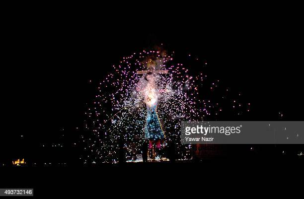 Kashmiri Pandits use sparklers to create shapes as they burn effigies of the demon king Ravana during the Dushera festival on October 22 2015 in...