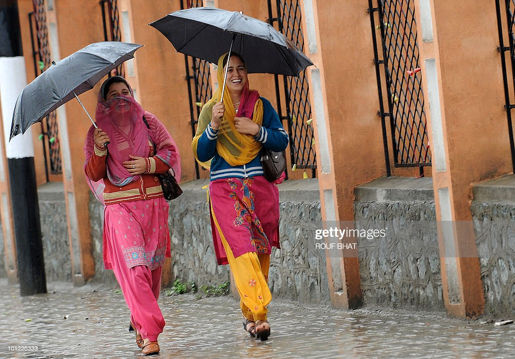 Kashmiri pedestrians walk through a rain shower holding umbrellas in Srinagar on May 28, 2010. Heavy rains have left the Kashmir Valley's rivers and streams swollen, prompting authorities to issue a flood alert. We are closely monitoring the water levels in the Jhelum and other rivers,' said an official from the flood control department. AFP PHOTO/Rouf BHAT