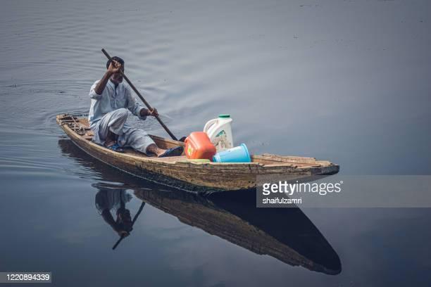 kashmiri people paddle a shikara (traditional wooden boat) at dal lake. - shaifulzamri stock pictures, royalty-free photos & images