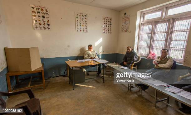 Kashmiri polling officials wait for people to cast their votes in a deserted polling station where the polling turn out was low during the third...