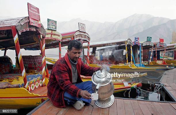 Kashmiri pours tea from a samovar next to shikaras in Dal Lake on November 19 2009 in Srinagar the summer capital of Indian held Jammu and Kashmir...