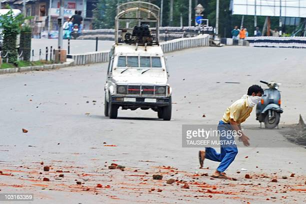 Kashmiri protester flees a police vehicle during clashes in Srinagar on July 30, 2010. Violent clashes between Kashmiri protesters and Indian police...