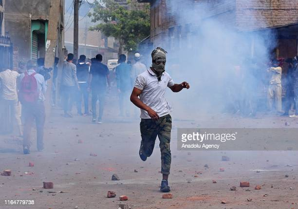Kashmiri protester runs after police used tear gas shells during a protest against India's revoking of Article 370 of its constitution in...