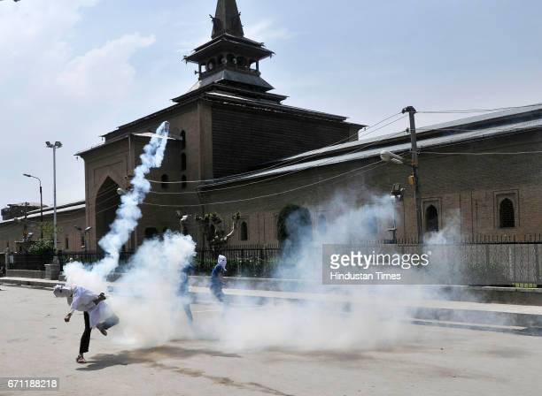 Kashmiri protester throw exploded tear gas shell back at policemen during a protest outside Jamia Masjid Kashmir's Grand Mosque on April 21 2017 in...