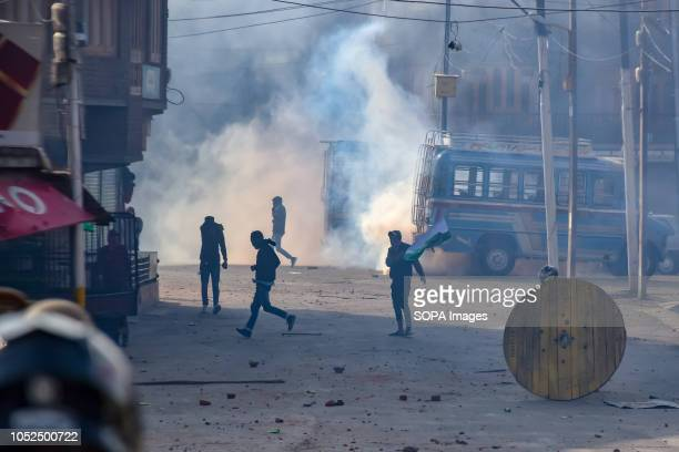 Kashmiri protesters are seen standing amidst teargas smoke during clashes that erupted in the main city in disputed Kashmir after a gun battle...