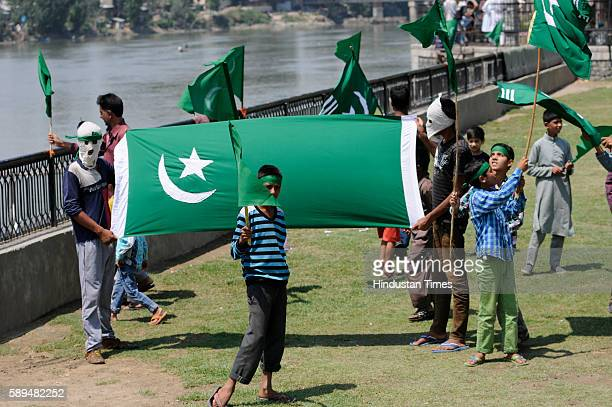 Kashmiri protesters hold a flag of Pakistan during the occasion of Pakistan's Independence Day celebration on August 14 2016 in Srinagar India...