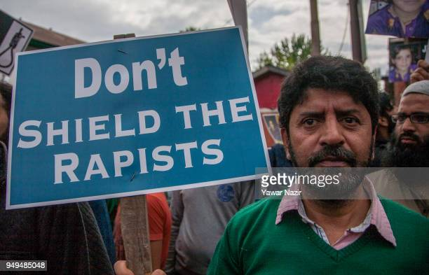 Kashmiri protesters hold placards during a protest against the rapeandmurder of a minor Muslim girl on April 21 2018 in Srinagar the summer capital...