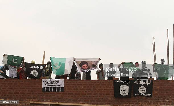 Kashmiri protesters shout antiIndia and proPakistan slogans as they hold Pakistani ISIS LashkareTaiba flags and a picture of ISIS leader Abu Bakr...