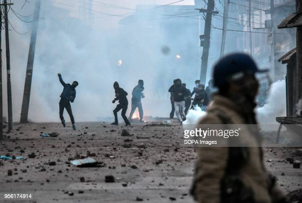 Kashmiri protesters throw stones amid tear smoke during clashes with government forces in Srinagar Indian administered Kashmir Fierce clashes broke...