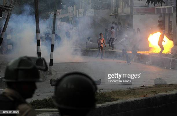 Kashmiri protesters throw stones at security men as a tear gas shell explodes near them during clashes in the downtown area of Srinagar on September...