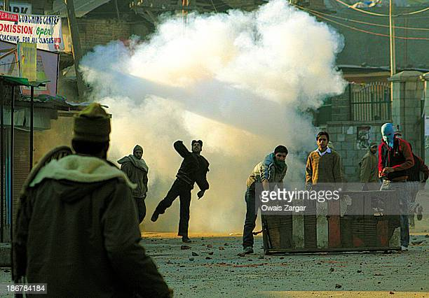 Kashmiri protesters throwing stones towards Indian police during a protest in Srinagar to condemn the assassination of Pakistan's former prime...