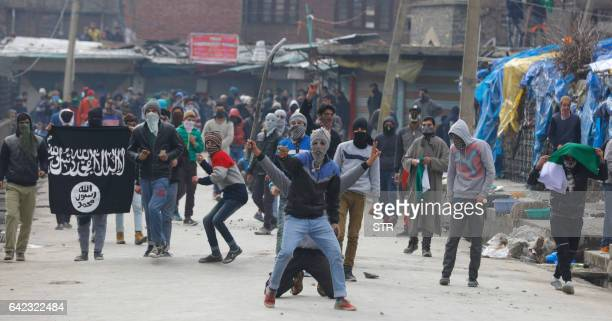 Kashmiri protesters wave an ISIS flag and throw stones towards Indian security forces during clashes in Srinagar on February 17 2017 Indian police...