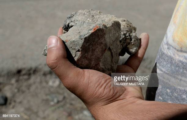 Kashmiri protestor holds a rock during clashes with Indian government forces in Srinagar on June 9, 2017. The death of a student killed by troops in...