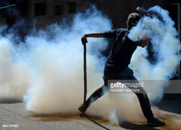 Kashmiri protestor throws back a teargas canister at Indian government forces during clashes in Srinagar on June 9 2017 Another student death in...