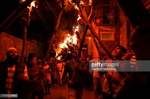 Kashmiri protestors hold torches as they shout antiIndian and profreedom slogans during a protest at Anchar Soura in Srinagar on September 26 2019