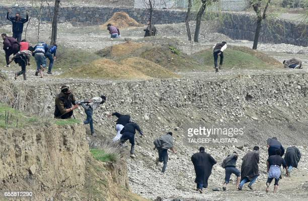 Kashmiri protestors run after Indian security personnel used live ammunition near the site of a gun battle between suspected rebels and Indian...