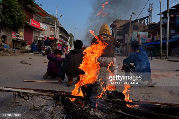 TOPSHOT Kashmiri protestors shout anti Indian slogans infront of burning tyres during a lockdown in Srinagar on October 272019which commemerates the...