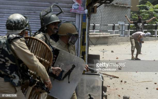 TOPSHOT Kashmiri protestors throw stones towards Indian government forces during clashes in Srinagar on July 8 2017 India on July 8 imposed a...