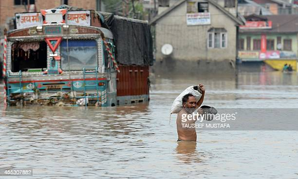 A Kashmiri resident carries belongings through floodwaters past an inundated truck in central Srinagar on September 12 2014 The main city in Indian...