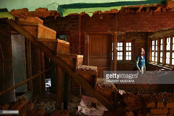 A Kashmiri resident is pictured inside a house damaged by flooding at Chak village south of Srinagar on September 15 2014 Fresh rain hampered rescue...