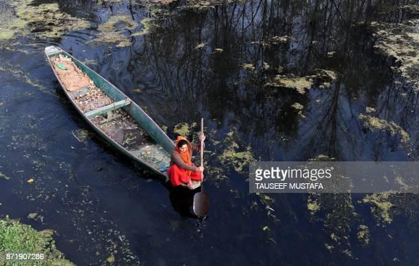 A Kashmiri resident rows a boat across Dal Lake in Srinagar on November 9 2017 / AFP PHOTO / Tauseef MUSTAFA