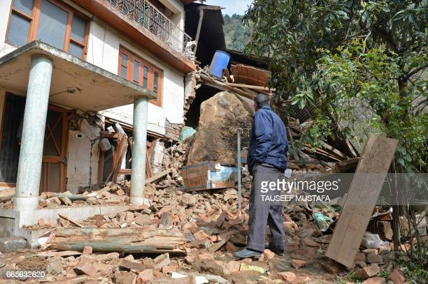 Kashmiri resident stands near a house damaged by a landslide which police said damaged three properties near the Shankaracharya Hill at Gagribal on...