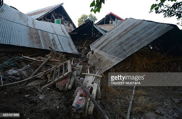 A Kashmiri resident walks past a house damaged by flooding in Rakshalana south of Srinagar on September 15 2014 Rescuers struggled to reach more than...