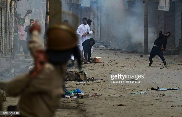 Kashmiri residents and Indian police clash in Srinagar on October 6 2014 Eid festivities were muted in Kashmir devastated last month by heavy monsoon...