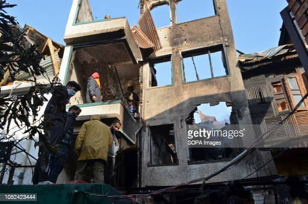 Kashmiri residents are seen inspecting a house that was damaged during the clashes Clashes broke out between militants and government forces in...