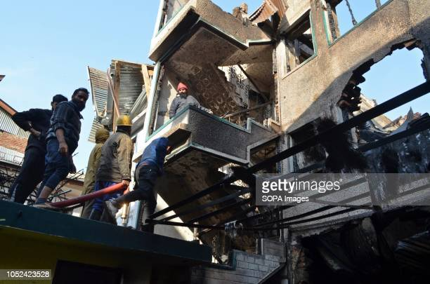 Kashmiri residents are seen inspecting a house that was damaged during the clashes Encounter broke out between militants and the government forces in...