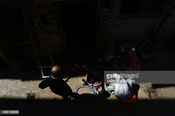 Kashmiri residents clean salvaged utensils from their residence following flooding in central Srinagar on September 26 2014 The floods which hit on...